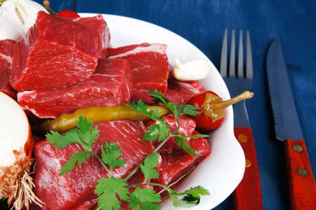 circular muscle: raw fresh beef meat slices in a white bowls with onion and red peppers serving on blue table with cutlery