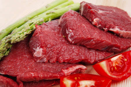 fresh raw beef meat steak fillet on wooden plate with asparagus and tomatoes ready to prepare isolated over white background photo