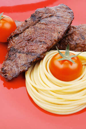 meat grilled: Meat grilled beef steak with pasta and tomatoes on red plate isolated over white