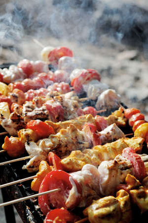 kebab: chicken shish kebab on bbq grill in sauce on skewers with tomatoes and peppers Stock Photo