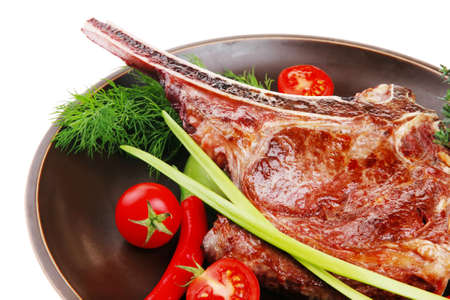 meat food: meat food : roast rib on dark dish with thyme pepper and tomato isolated over white background