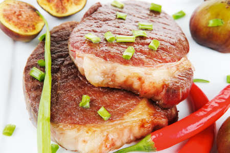entree: meat entree : grilled beef steak served with red hot cayenne peppers green chives and sweet figs on plate isolated over white background Stock Photo