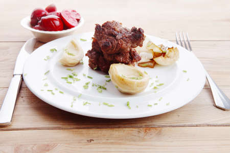 traditionally american: beef bourguignon in wine with artichoke and marinated vegetables on white plate over wooden table