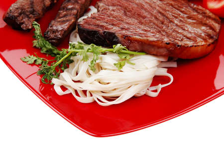 italian cuisine : grilled steak with pasta and tomatoes on red plate isolated over white background photo