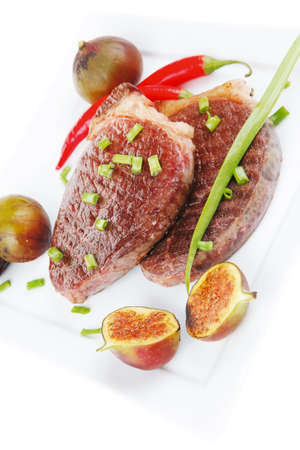 entree: main entree : roasted beef lamb steak served with hot cayenne peppers green chives and sweet figs on plate isolated over white background Stock Photo