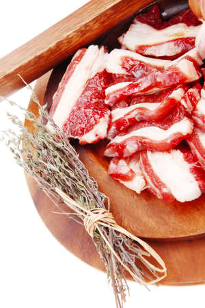 flesh eating animal: raw beef asado ribs with thyme and tomatoes on wooden board isolated over white background Stock Photo