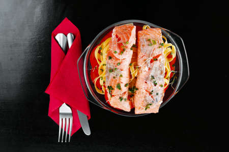 fresh fried natural pink salmon on italian traditional tagliatelles backed with tomato and vegetables served over black wooden table photo