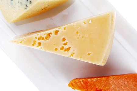 fresh aged french cheese parmesan roquefort and gruyere chops on white plate with isolated over white background photo
