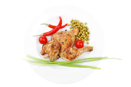fine legs: barbecued meat : chicken ham garnished with green onion pens and red chili hot pepper on white plate isolated over white background Stock Photo