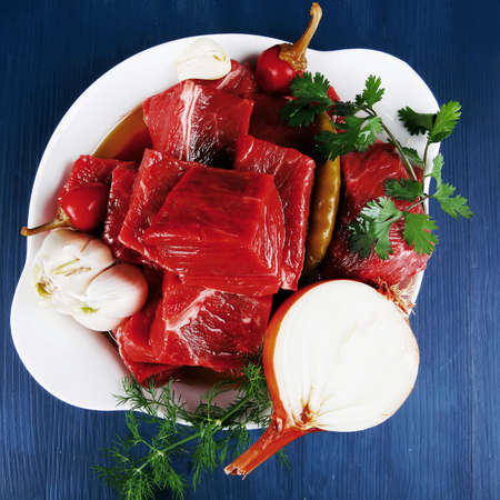 circular muscle: fresh uncooked beef meat slices over white bowls ready to prepare with red peppers and greenery serving on blue table with cutlery