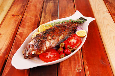 sunfish: healthy lunch : whole fried sea sunfish on wooden table with lemons peppers and tomatoes and rosemary twig