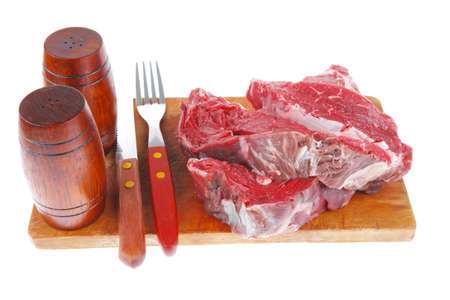 pepper castor: fresh raw beef steak entrecote fillet ready to prepare on cut board with cutlery and castor isolated over white background