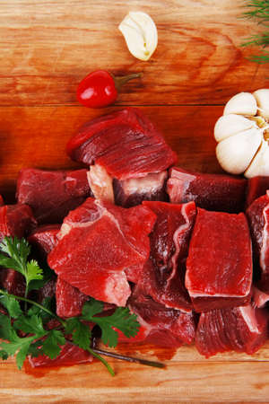 circular muscle: fresh raw beef meat slices over a wooden board with dill , green  and red hot peppers isolated over white backkground Stock Photo