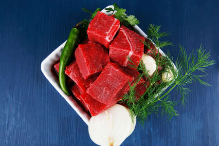 circular muscle: uncooked fresh beef meat chunks on white bowls with green hot peppers and vegetables serving over blue wooden table