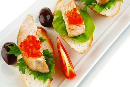 king salmon: healthy appetizer : sandwich with sea salmon and red caviar, olives, tomato and lemon on white china plate isolated over white background Stock Photo