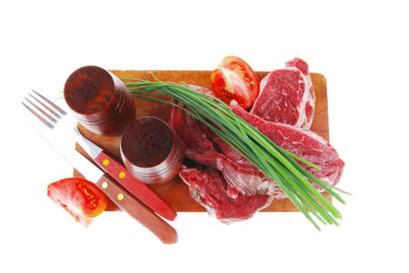 crushed red peppers: main course : fresh raw beef steak entrecote ready to prepare on cut board with green chives and tomatoes isolated on white background