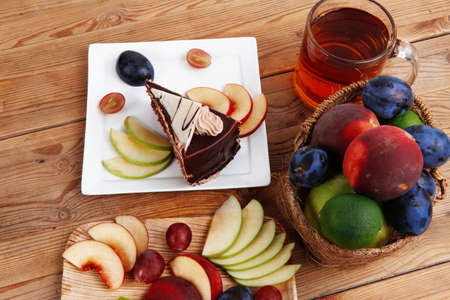 summer pudding: slice of chocolate cream brownie cake topped with white chocolate and cream flowers with hot tea mug decorated with fruits apple plum and grape on plate on wooden table Stock Photo