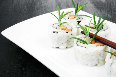 soysauce: Japanese Cuisine - California Roll made of Salmon, Cream Cheese and Avocado inside. Served with wasabi and ginger on long white plate over black table