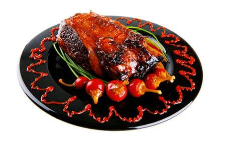 adn: asado de carne roja beef bloque servido en un plato negro con cebollines verdes adn ají rojo en plato negro aislado sobre fondo blanco