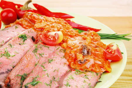 corned beef on plate with vegetables over wooden table photo