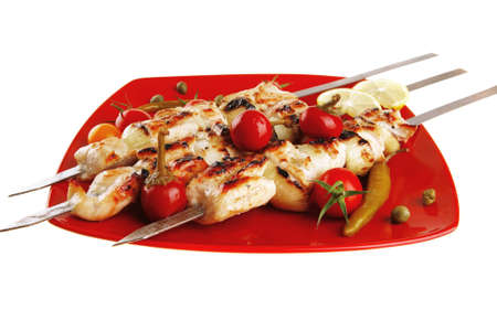 bbq grill: fresh grilled chicken shish kebab served wtih tomato cherry hot peppers on skewers over red plate isolated on white background