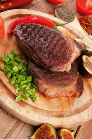 green stuff: roasted beef lamb steak served with hot cayenne peppers green stuff sweet figs and cutlery on wood plate over wooden table Stock Photo