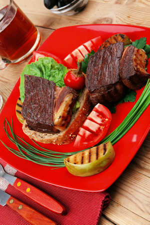 beef fillet mignon grilled and garnished with vegetables , juice and olives on red plate over wooden table photo