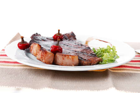 steak beef: new york meat style beef steak fillet on white plate with hot chili pepper and green salad isolated over white background with stainless steel cutlery Stock Photo