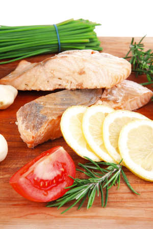 entree: savory sea fish entree : roasted salmon fillet with green onion, red cherry tomatoes pieces, rosemary twigs and lemon on wooden board isolated on white background