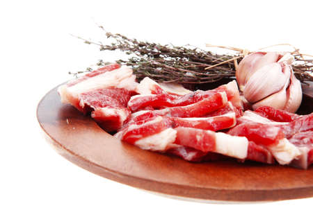 flesh eating animal: raw ribs with thyme and garlic on wooden isolated over white background
