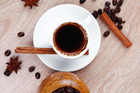 arabic coffee: sweet hot drink : black arabic coffee in small white cup with mortar and pestle , beans spilled over wooden table , decorated with cinnamon sticks and anise stars