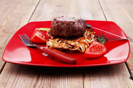 free business: grilled beef fillet pieces on noodles , red hot chili pepper with tomato on red plate over wood table Stock Photo