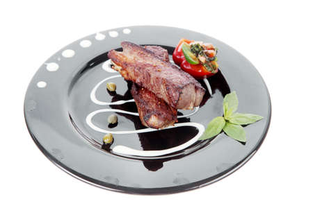 nightime: fresh red beef meat steak barbecue garnished vegetable salad sweet potato and basil on black plate isolated over white background