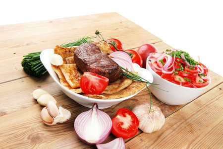 meat food: meat food : roasted fillet mignon on bread in white bowl garnished with tomatoes salad on wooden table Stock Photo