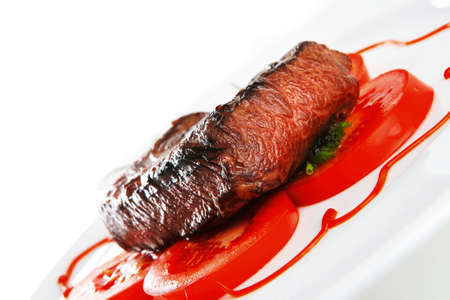 carne asada: filete de carne de vacuno de carne entrecot servido con tomate y cebollín verde sobre plato de porcelana blanca aislados sobre fondo blanco