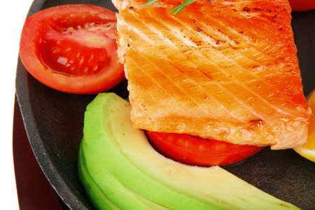 healthy sea food: grilled salmon on iron pan over wooden plate with lemon avocado and tomatoes isolated on white background photo