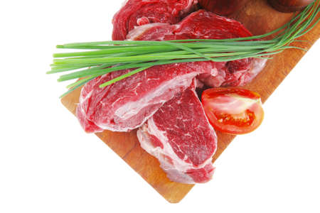 main board: main course : fresh raw beef steak entrecote ready to prepare on cut board with green chives and tomatoes isolated on white background