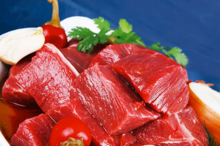 circular muscle: slices of raw fresh beef meat fillet in a white bowls with garlic and red peppers serving on blue table with cutlery
