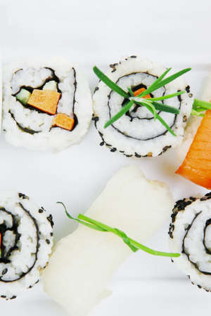 soysauce: California Roll with Avocado and Salmon, Cream Cheese and Raw Salmon inside. on long white plate . isolated over white background . Maki Sushi and Sashimi