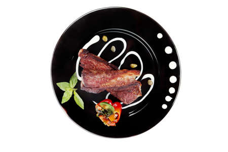 barbequing: fresh red beef meat steak barbecue garnished vegetable salad sweet potato and basil on black plate isolated over white background