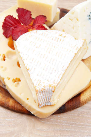 edam: edam parmesan and brie cheese on wooden platter over wooden table