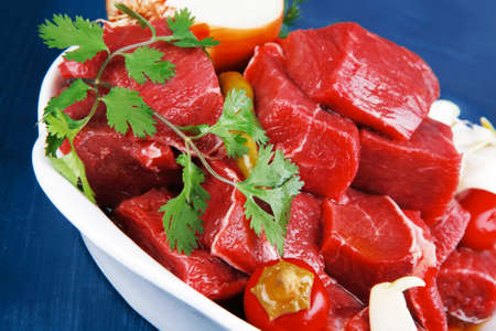 circular muscle: uncooked fresh beef meat chunks on white bowls with vegetables and red peppers serving on blue table with cutlery Stock Photo