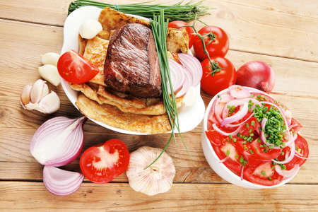 side of beef: beef garnished with tomatoes salad in bowl, green chives and tomatoes on side on wooden table