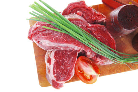pepper castor: fresh raw beef steak entrecote ready to prepare on cut board with green chives and tomatoes isolated on white background Stock Photo