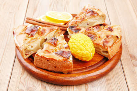 custard slices: cuts of apple pie on wooden plate with cinnamon sticks and lemons