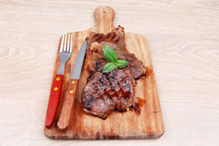 served beef meat barbecue on wooden plate with cutlery photo