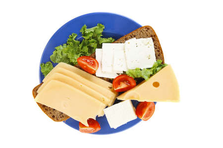 set of gourment cheese slice and chunk ( bar)  white goat greek yellow french aged on half of rye bread on green lettuce salad with tomatoes on blue plate isolated over white background photo