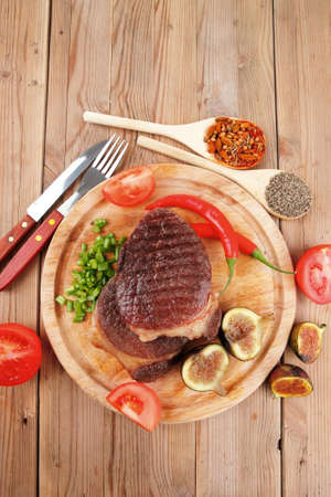 green stuff: grilled beef steak served with red hot cayenne peppers green stuff sweet figs and cutlery on wood plate over wooden table