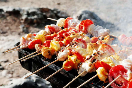 kebob: chicken shish kebab on bbq grill in sauce on skewers with tomatoes and peppers Stock Photo