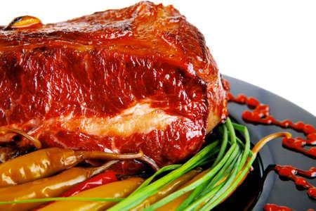 adn: asado de carne roja beef bloque servido en un plato negro con cebollines verdes adn aj� rojo en plato negro aislado sobre fondo blanco
